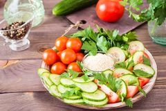 Fresh slices of cucumbers, tomatoes, sesame seeds in a bowl. And parsley leaves on a plate on a wooden table. Oil and seasoning for cooking vegetable salad Stock Photo
