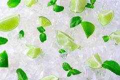 Fresh slices of green limes and mint over crushed ice cubes Stock Photos