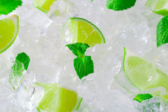 Fresh slices of green limes and mint over crushed ice cubes Stock Image