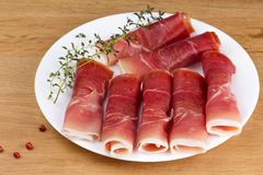 Fresh slices of jamon on a plate. With thyme and pepper Royalty Free Stock Images