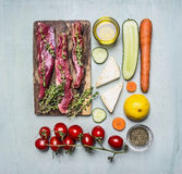Fresh slices of raw lamb with herbs, spices, oil and lemon and vegetables on the cutting board lined rectangle on wooden rustic ba Royalty Free Stock Photo