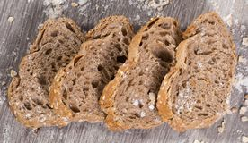 Fresh slices of rye bread on wooden surface. Four fresh slices of rye bread on wooden surface Royalty Free Stock Photography