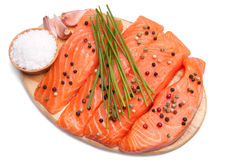 Fresh slices of salmon. Fresh slices of red salmon with color pepper, garlic, chives  and sea salt  on cutting board Stock Photography
