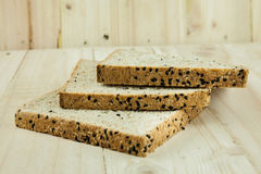 Fresh slices of wholewheat bread with various seeds and multigra. In on wood background Stock Image