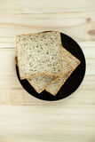 Fresh slices of wholewheat bread with various seeds and multigrain. On the black plate in wood background Stock Photos