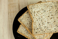 Fresh slices of wholewheat bread with various seeds and multigrain. On the black plate in wood background Stock Photography