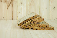 Fresh slices of wholewheat bread with various seeds and multigrain. On wood background Royalty Free Stock Images
