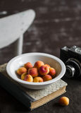 Fresh small apricots on a white plate, a book and an old camera. On a dark fabric background Stock Photo