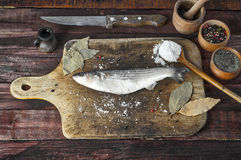 Fresh smelt fish  on the kitchen cutting board. Fresh smelt fish with salt and pepper on the kitchen cutting board, view from the top Royalty Free Stock Photos