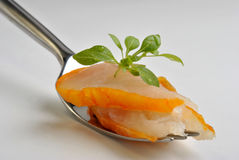 Fresh smoked salmon on a fork. Some fresh smoked salmon on a fork with greek basil Royalty Free Stock Images