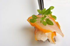 Fresh smoked salmon on a fork with greek basil. Some fresh smoked salmon on a fork with greek basil Stock Images