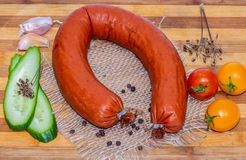 A fresh smoked sausage horseshoe shape with bacon and sliced green cucumber and three red and yellow tomatoes cherry and. Black pepper peas and seeds of dill royalty free stock photo