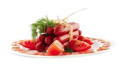 Fresh smoked sausages on plate Stock Image