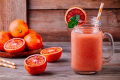 Fresh smoothie with  banana, blood oranges and mint in a mason jar. Fresh smoothie drink with  banana, blood oranges and mint in a mason jar on a wooden rustic Stock Photo