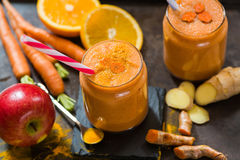 Fresh smoothie with carrot, apple, orange, banana, ginger and tu Stock Photography