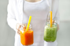 Fresh smoothie detox vegetable carrot lettuce and cucumber in hands on the pastel background Stock Photography