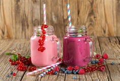 Fresh smoothies, close up. Two jars mug of milkshakes of different berries ( redcurrant, blueberry, raspberry)on a old wooden table Royalty Free Stock Photo
