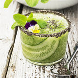 Fresh smoothies from cucumber, mint and honey in a glass are decorated with edible flowers of a garden viola. Selective Royalty Free Stock Image