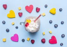 Fresh smoothies with raspberry, kiwi and bananas on a blue background, with  expansion of multi-colored hearts around, healthy Stock Images