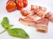 Fresh snack of dry smoked ham tomato and basil isolated on white Royalty Free Stock Image