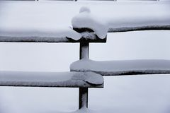 Fresh snow filled corral fences at rural winter snowy horse farm Stock Image
