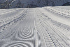 Fresh snow groomer tracks on a ski piste Royalty Free Stock Photos