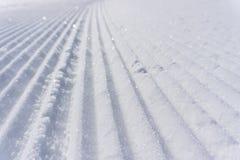 Fresh snow groomer tracks on a ski piste Royalty Free Stock Image