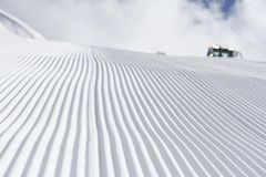 Fresh snow groomer tracks on a ski piste Stock Photo