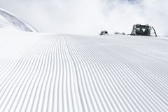 Fresh snow groomer tracks on a ski piste Royalty Free Stock Photo