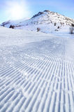 Fresh snow groomer tracks on a ski piste with sky background Royalty Free Stock Photo