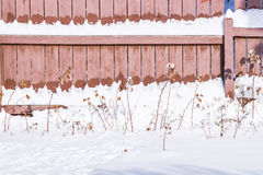 Fresh snow is  melting on the sun heated wood fence Stock Photos