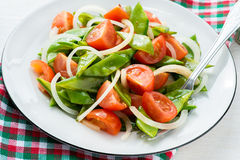 Fresh snow peas and tomato salad on plate Royalty Free Stock Image