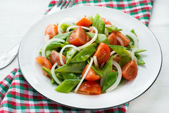 Fresh snow peas and tomato salad on plate Royalty Free Stock Photos