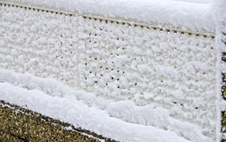 Fresh snow sticks on a garden fence Stock Photo