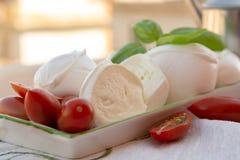 Fresh soft Italian white cheese mozzarella buffalo, original fro. M Campania, Paestrum and Foggia regions, South Italy, served with tomatoes and fresh basil stock photos