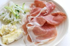 Prosciutto ham with cheese and salad in white background Stock Photos