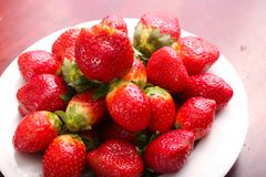 Fresh some strawberries. Fresh strawberries fruits on white dish on wooden table Stock Photo