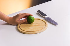 Fresh and sour green lime or lemon, half cut with knife on chopp Stock Photo