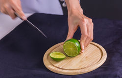Fresh and sour green lime or lemon, half cut with knife on chopp Royalty Free Stock Photo