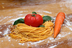Fresh spaggeti with tomato and carrot. On wooden table Royalty Free Stock Photo
