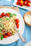Fresh spaghetti meal. Plate filled with spaghetti, crushed tomatoes, basil and parmezan Stock Image