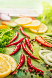 Fresh spices and herbs with lemon on green background Royalty Free Stock Photography