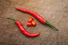 Fresh and spicy cayenne with cup out sections on wooden chop board Stock Images