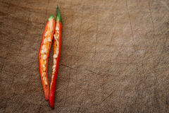 Fresh and spicy cayenne cut out on wooden chop board Stock Images