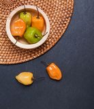 Fresh spicy habanero peppers of different colors in a small wooden bowl stock images
