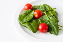 Fresh spinach and cherry tomatoes Royalty Free Stock Images