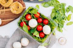 Fresh spinach and cherry tomatoes with mushrooms and pasta. Raw vegetable. natural plant leaf. healthy and vegetarian or. Organic bio food. top view. close up Stock Images
