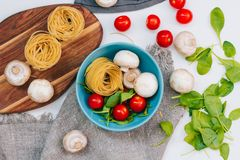 Fresh spinach and cherry tomatoes with mushrooms and pasta. Raw vegetable. natural plant leaf. healthy and vegetarian or. Organic bio food. top view. close up Royalty Free Stock Photo
