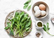 Fresh spinach, garlic, ramson and organic farm eggs on white background, top view - healthy  food ingredients. Flat lay Royalty Free Stock Image