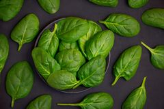 Fresh spinach leaves in bowl on dark background. Top view.  stock photo